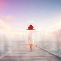 Spiritual conceptual image of a female angel standing barefoot on an ocean jetty in a white dress with a halo and outspread wings showing motion blur with ethereal colorful sun flare effects